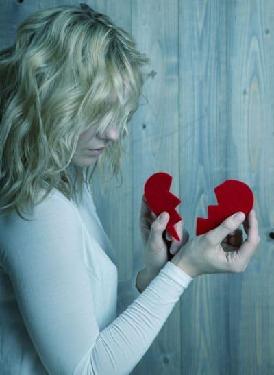 liebeskummer: Frau mit zerbrochenem Herz in den Händen